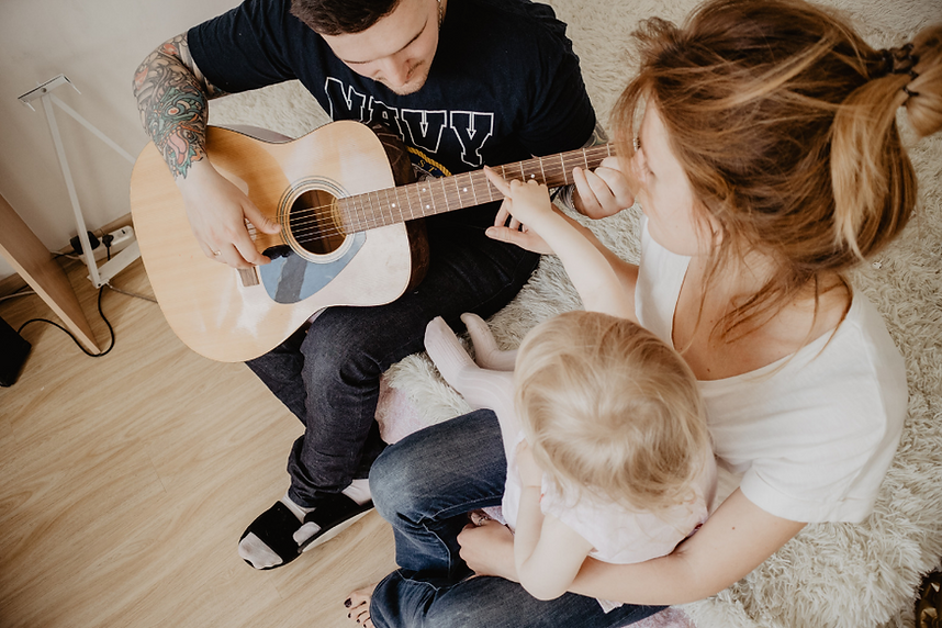 a mother and father singing a song to their baby while dad plays the guitar