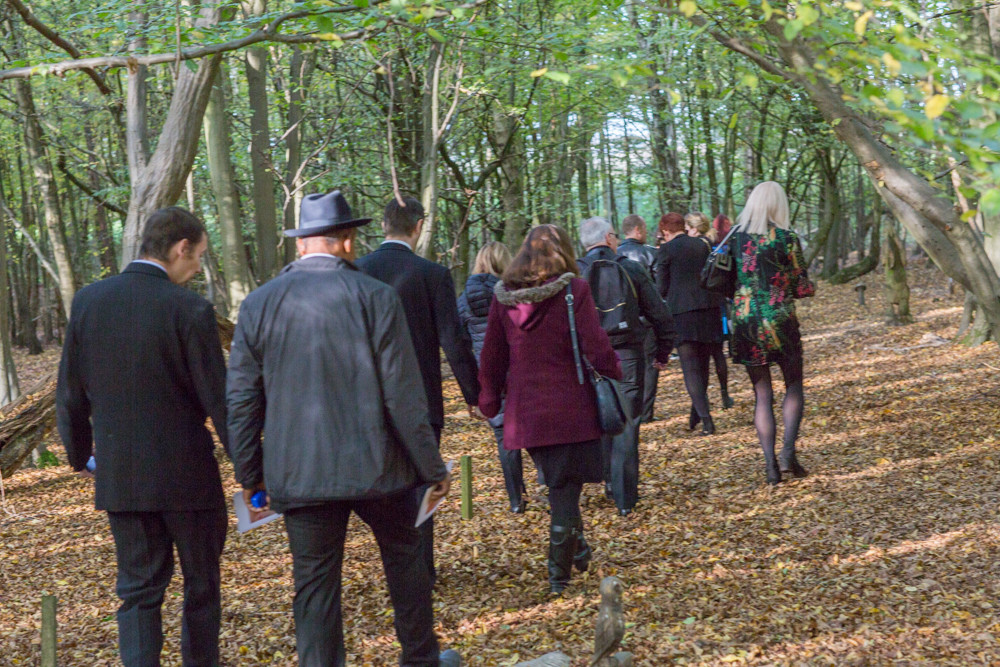 Mourners walking through woodland to the graveside at a natural burial ground