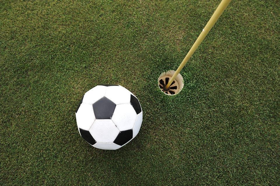 Football big ball at golf field hole.jpg