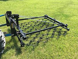 Three Point EconoDrag chain harrow aerating a pasture