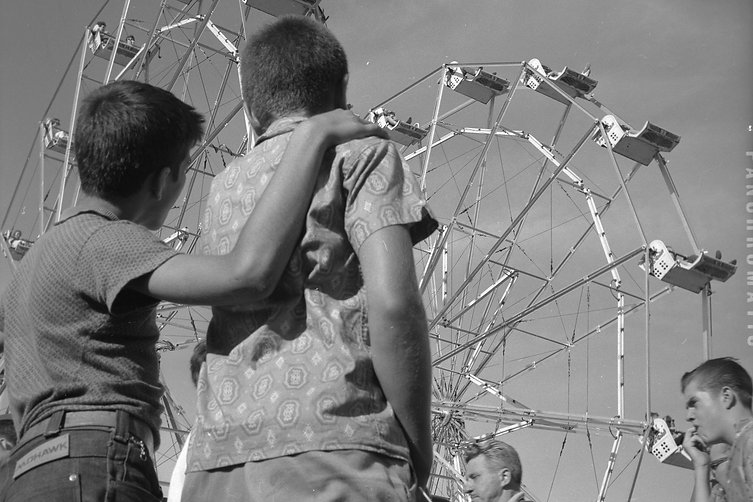 Image of two people at the CNE looking at a Ferris Wheel. Image is in black and white