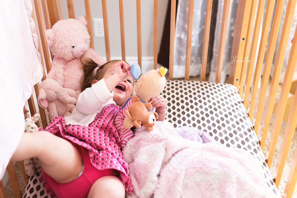 Laughing with her favourite baby doll in her crib | Medicine Hat Lifestyle Family Photographer