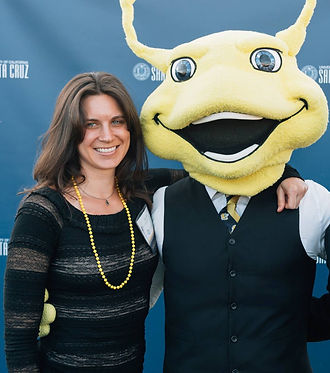 Tisha smiling with her arm around tha person dressed as UCSC's mascot, Sammy the banana slug shoulder