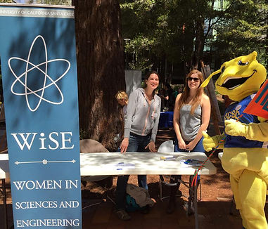 Tisha behind a table with fellow WiSE member and a person dressed as UCSC's mascot, the banana slug, in a Sammy Slug costume banana slug costume during DNA day, 2015.