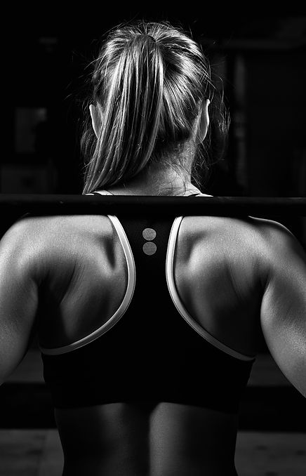 Back view young female doing barbell squ
