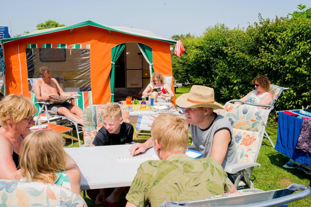 Familie De Vreede. Van links naar rechts met de klok mee: Wendy(44), Robert(47), Joyce(16), Monique(39), John(45), Luke(16), Rocco(10), Anouk(12) op camping 'De Koningshof' in Rijnsburg.  Monique: 'Al 10 jaar lang komen we op deze camping. Rocco was net geboren toen we hier voor het eerst kwamen. Het leek ons leuk om met de beiden gezinnen het Pinksterweekend te vieren, John en Robert zijn broers. Tussen de vakanties door wordt er hard gewerkt: John is automonteur en Robert is als vrachtwagen chauffeur vaak lang weg van huis. We wonen in Nootdorp, hier ongeveer een halfuur rijden vandaan. Dat we niet een halve wereldreis maken om te ontspannen is vooral praktisch: als we richting het zuiden rijden staan we toch alleen maar in de file. En waarom ver weg gaan als je een halfuur van huis ook helemaal een vakantiegevoel kan hebben? Ons hoogste doel hier op de camping is ontspannen, we zetten de caravans neer, we bouwen de tenten op, klappen de stoelen uit, we gaan zitten en we komen het terrein niet meer af. We doen alleen nog even boodschappen, de eerste dag dat we hier aankomen. En dan begint het grote genieten: spelletjes spelen, naar het zwembad, samen koken, borrelen en ook een keertje naar de snackbar hier op de camping. Veel heb je ook helemaal niet nodig als je met elkaar bent, zelfs geen gezellige buren of camping vriendinnen.' Wendy: 'We hebben weleens naast gezinnen gestaan die niet op ons zaten te wachten. Zij hadden een seizoensplek en stonden daar dag in dag uit, jaar na jaar. Ze zagen ons, als vakantiegangers, als indringers. Hun kinderen negeerden onze kinderen en zagen het veld echt als hún terrein. Prima: wij hebben genoeg aan onszelf. Inmiddels hebben we op deze camping op verschillende velden gestaan, en door schade en schande hebben we nu de beste plek van de camping. Hier kan niets meer mis gaan; we hebben aan een kant schaduw en aan een kant zon. Zo is er altijd wat te kiezen. En we zitten dicht naast het sanitair, wat wel zo makkelijk is. Ieder j