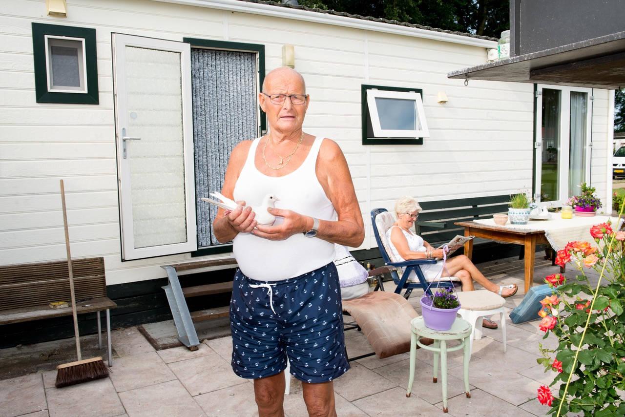 Familie van Montfort op camping Strandbad in Edam. Op de foto van links naar rechts Simone (37) Alie (71), Marcel (51), Dennis (48), Peter (78) en Dina (3)  Alie: 'We komen hier al ruim 20 jaar. Eerst hadden we een oudere caravan, maar sinds een paar jaar dit geheel nieuwe chalet waar het net zo comfortabel is als bij ons thuis. Daarom wonen we hier minstens vier maanden per jaar. Vanaf april, wanneer het seizoen begint, tot het einde van de zomer. Alles gaat mee, ook ons parkiet die hier een mooi uitzicht heeft over het Ijsselmeer. We hoeven niet bang te zijn dat de plantjes dood zijn als we thuiskomen, we wonen hier heel dichtbij in Volendam. Peter gaat iedere ochtend op de fiets naar ons huis om te douchen, de post te halen en de plantjes water te geven. Dat we zo dichtbij huis zijn is niet gek, de meeste mensen hier op de camping komen uit Volendam of Edam. Het straatje waarin ons chalet staat heet ook het Volendammerlaantje, dat is niet helemaal toevallig. Dat iedereen uit de omgeving komt is niet alleen heel gezellig, maar vooral ook praktisch; als we hier naartoe komen staan we nooit in de file en toen we nog werkten konden we vanaf hier naar ons werk fietsen. Dan fietste we na het werk hier de dijk over en dan hadden we weer vakantie. Inmiddels zijn we gepensioneerd en genieten we van de rust en van het mooie IJsselmeer waar we praktisch aanstaan. Vroeger hadden we een zeilboot, maar nadat Peter nieuwe heupen kreeg werd dat een te riskante hobby. Het water blijft ons altijd trekken, hoewel we op deze plek soms ook de nadelen van het water te zien krijgen. Kort geleden nog is de halve camping overstroomd door de hoogwaterstand en stond het water 60cm hoog tot aan je knieën. Gelukkig staat ons chalet op een heuveltje en hebben we weinig schade opgelopen. En ook die keer toen de eigenaar van de camping ons midden in de winter in paniek op belde - of we direct konden komen – werden we verrast door het IJsselmeer. Toen we aankwamen stonden de ijsschotsen tot aan 