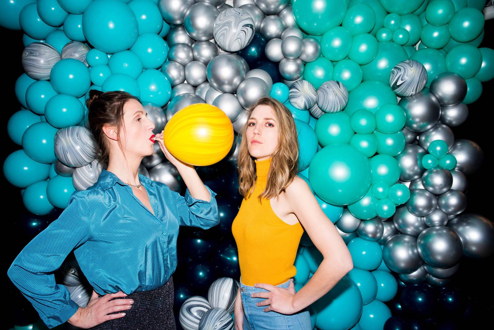Femke (36) en Marjolein (33) uit Amersfoort. Samen verzorgen zij met hun bedrijf Your Balloons de ballonstyling op exclusieve feesten, evenementen en festivals.   Femke: 'Wat wij doen met ballonnen vult letterlijk de ruimte. Juist omdat het on-nederlands is om groots uit te pakken op feesten, zijn wij met onze ballonstyling pioniers op dit vlak en hebben we het gevoel dat de wereld aan onze voeten ligt. Opdrachtgevers zijn vaak blij met de exclusiviteit die we bieden, we hebben samengewerkt met merken als Moët, BWM en RTL. Ook stylen we met onze ballonnen grote evenementen in onder andere het Okura Hotel en het W Hotel in Amsterdam.' Marjolein: 'Onze particuliere klanten zijn voornamelijk mensen die veel waarde hechten aan het geven van een goed feest. Het wordt vaak onderschat wat een beetje  professionele aandacht voor een feest kan doen. Onze ballonneninstallaties kunnen een feest echt máken. Tegenwoordig vieren mensen meer dan alleen een verjaardag of bruiloft. We stylen regelmatig ook babyshowers en gender revealparty's met onze ballonnen. Femke: 'Het gekke is dat we vaak ergens binnen komen met niks - slechts een paar koffers gevuld met lege ballonnen - en wanneer we de ruimte verlaten is er echt iets wezenlijks veranderd.' Marjolein:   'Nederlanders zijn gewend om alles voor een feestje zelf te doen, ik denk  voornamelijk om geld te besparen. De meeste mensen denken; ik kan toch zelf wel een paar ballonnen opblazen? Maar als ze zien wat wij doen, komen ze daar gauw van terug.'