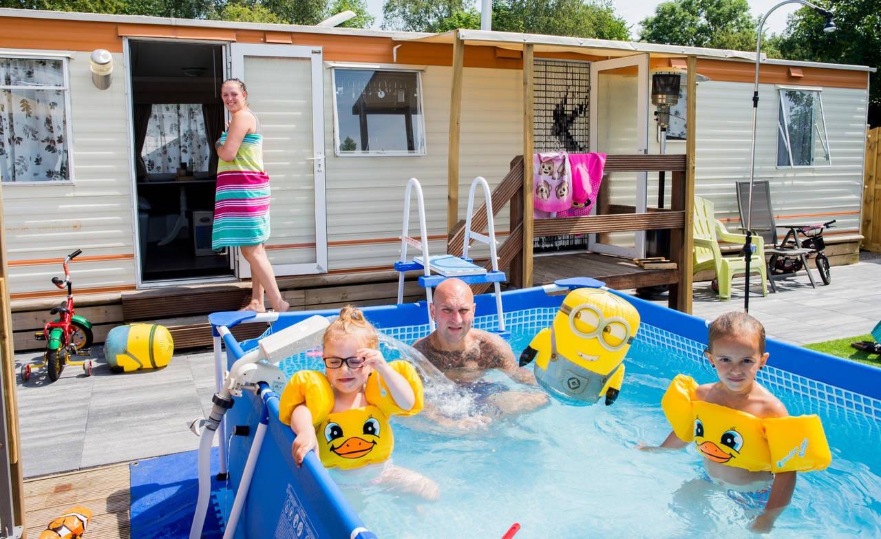 Familie Roerig/ Nauman op camping 'De Ursummer Plas' in Ursum. Priscilla (30), Dennis (38) en hun dochters La-Laicy (2) en Hope (3).  Priscilla: 'Gister hebben we voor het eerst het zwembad gevuld. Dat was eigenlijk de laatste klus die we nog moesten doen voordat het hier helemaal naar ons zin was. Vorig jaar kochten we deze sta-caravan en in een jaar tijd hebben we zo'n beetje alles opgeknapt en veranderd wat er was. Nieuwe schuttingen, nieuwe plafonds, het tuinhuis, de tegels in de tuin, windschermen, ga maar door. Ieder weekend reed Dennis op en neer - ook in de winter - om ons plekje hier helemaal af te krijgen.' Dennis: 'Inmiddels zit al ons spaargeld erin, tja. Je kan je geld ook op de bank laten staan, maar daar heb je tegenwoordig ook niks meer aan. Nu genieten we hier ieder weekend met z'n allen en komen we vooral toe aan ons rust. We hebben nogal een aantal roerige jaren achter de rug. Toen we elkaar 3 jaar geleden leerden kennen werd Hope binnen een jaar geboren. Priscilla heeft PCOS (een afwijking aan de eierstokken, red.) waardoor ze van de dokter hoorde dat ze via de natuurlijke weg nooit meer kinderen zou kunnen krijgen. Uit een eerder relatie heeft Priscilla nog een 13 jarige dochter, Destiny, en toen ze onverwacht zwanger bleek te zijn van Hope leek dat wel een wonder na het nieuws van de dokter. Priscilla: 'We waren dolgelukkig met de geboorte van Hope, maar 3 maanden later bleek ik wéér zwanger. Toen hebben we wel even gehuild, het was zo snel achter elkaar. Toch zijn we ervoor gegaan en kregen we nog een klein meisje; La-Laicy. Eigenlijk had ik haar Faith willen noemen, dat paste wel mooi in het rijtje van Destiny en Hope. Maar Dennis zag dat niet zitten. Het werd La-Laicy; met een knipoog vernoemd naar de luiigheid van haar vader. Het is hard werken met drie kinderen, helemaal met de baan van Dennis. Als keurmeester van containers is hij vaak weg van huis. Door zijn werktijden en de onrustige nachten wonen we in het dagelijks leven niet samen. I