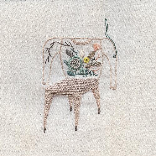 Silla con sweater con pájaro en jardín