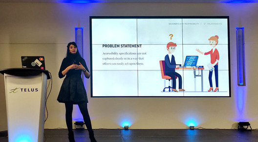 Hala on stage, presenting in front of a slide with the Problem Statement