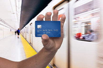 Hand holding a credit card in front of the subway