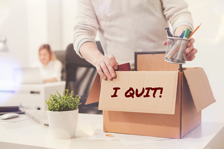 """Person packing up their desk at the Office into a box that reads """"I Quit!"""""""