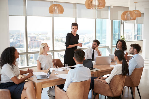 Businesswoman leads meeting around table of seven people