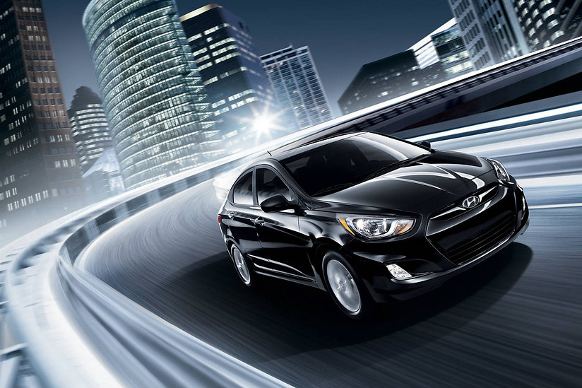 black hyundai accent sedan driving at night in the city