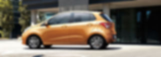 brand new Grand i10 Fluid in golden orange standing still.
