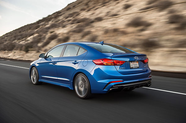 brand new hyundai elantra turbo sport in blue driving on the road