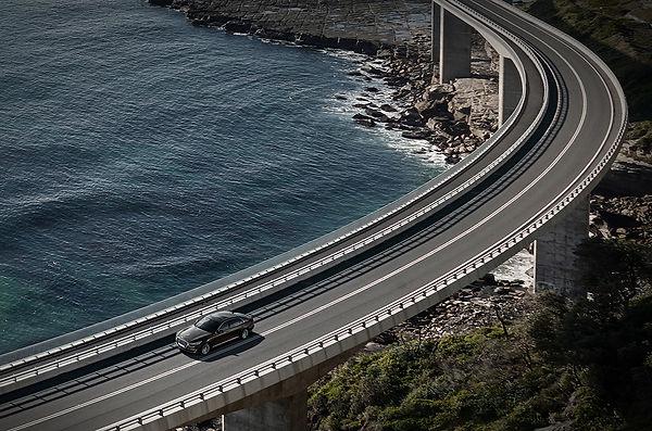 Sedan driving on a bridge.