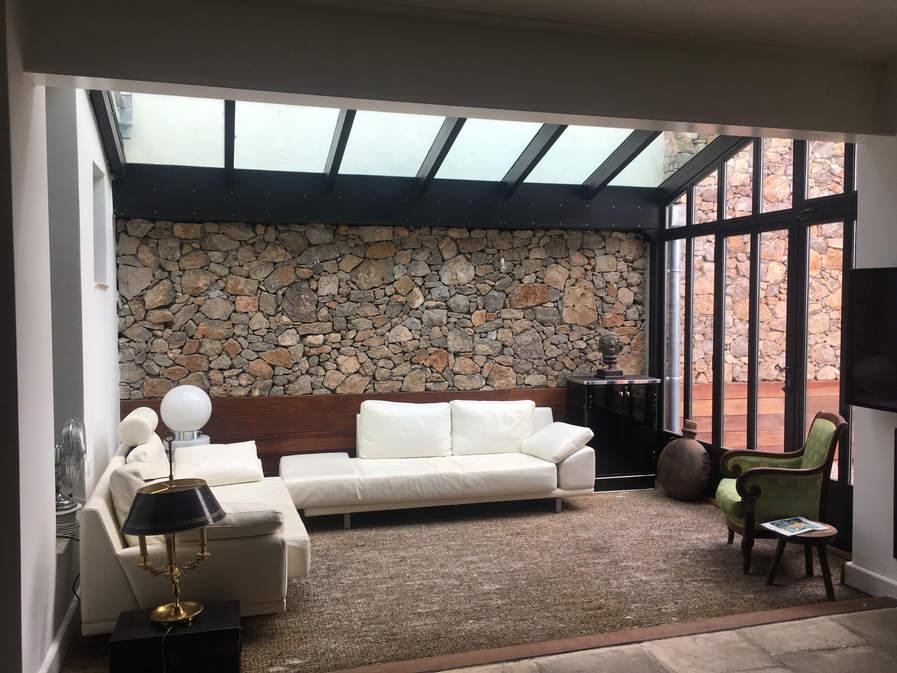 toiture vitrée et mur de pierres
