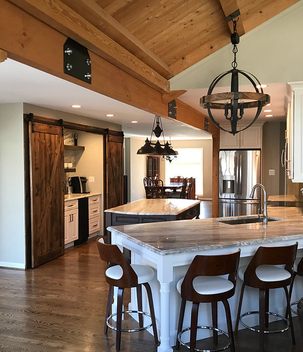 Amazing White Kitchen with Dark wood floors and barn doors.  Custom Walnut Furniture Style Island