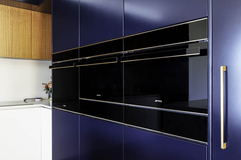 Navy kitchen with black ovens.