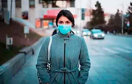 mujer con máscara en una calle desierta