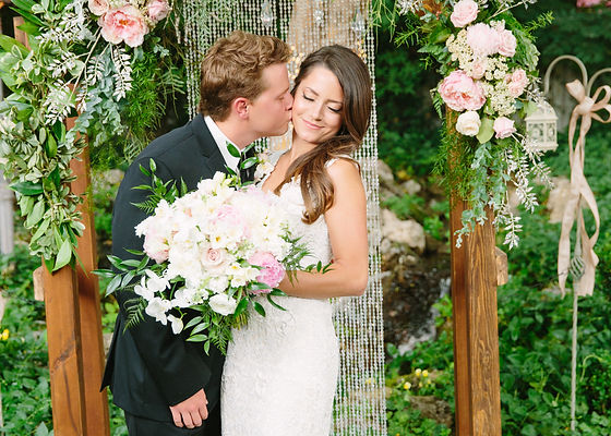 Beautiful June weddng with blush-colored flowers and elegant attire.