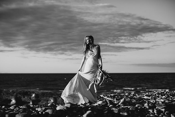 Bride looking at the sunset holding bouquet