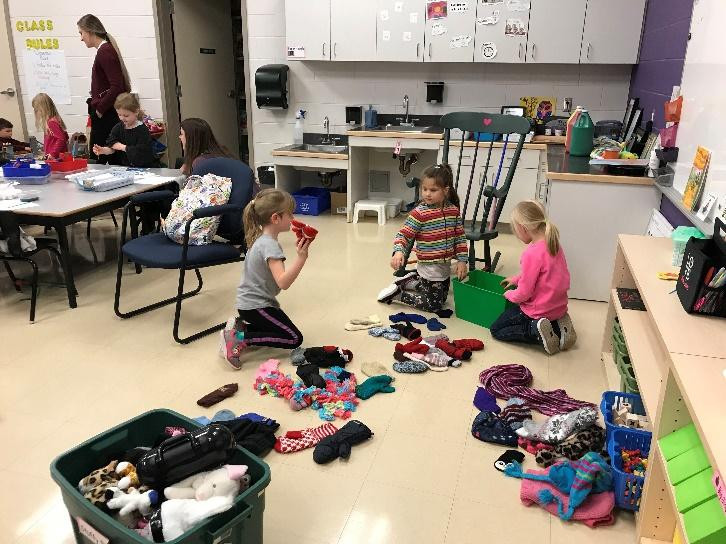 Here are my own students sorting socks and mittens for the stuffed toys in the Veterinarian center while another friend joins in.
