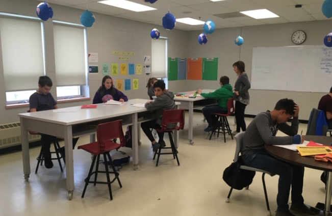 The tables are tall enough that students can stand comfortably to work or sit on a stool.