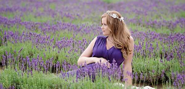 Memorable maternity photograph of in purple dress sitting in Laveannes' large lavender field.