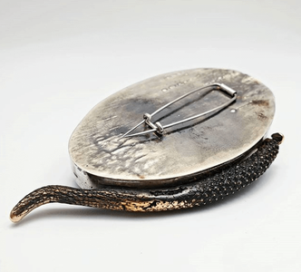 Wabi-sabi brooch shown from the back showing steel pin on silver surface