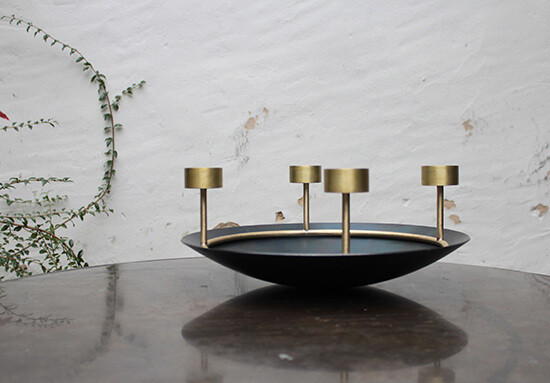 advent wreath made from brass that can hold four candles, sitting on a table