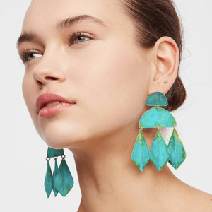 woman wearing bright green patina earrings in the shape of half circles and diamonds