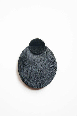 Brooch in the shape of a circle made with black animal hair