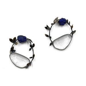 Earrings in the shape of a vine plant with a clear and blue stone