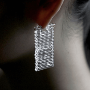 woman wearing rectangle earrings made of glass cylinders stacked on top of each other
