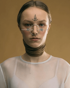 woman with tribal tattoos on her face wears a silver circle that fits on her nose