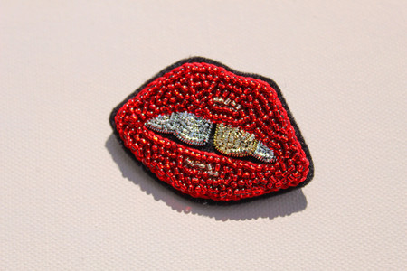 Brooch in the shape of red lips with teeth, made with red, silver and gold beads