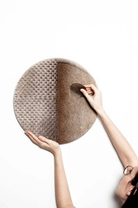 Woman combing a large wall hanging made from brown, short animal hide