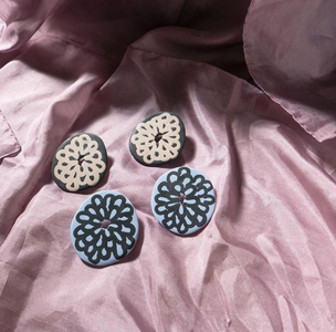 Blue and black polymer clay circle earrings with flower patterns painted on the surface