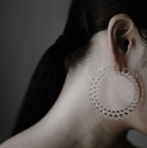 Woman wearing glass hoop earrings made of small glass circles connected together