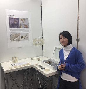 Xuewen Yao standing next to her exhibition space