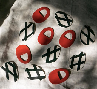 Red oval earrings and white oval earrings with black criss-crosses painted on the surface