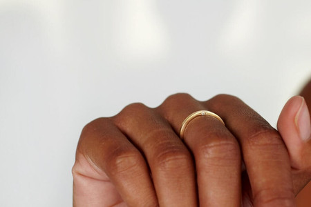 gold ring with diamond set on the side of the ring instead of on top, worn on a person's hand