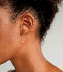 Woman wearing earrings made of fine gold wire bent into an oval shape
