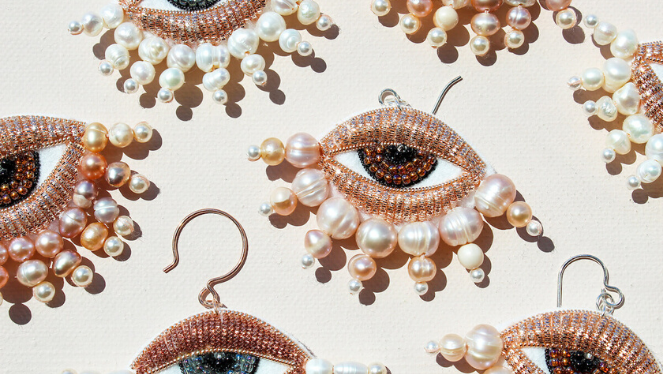 Many earrings lying on a white background, earrings are beaded in the shape of eyes