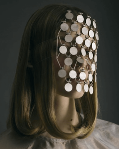 woman wearing mask made up of identical discs that fall across the face like lace