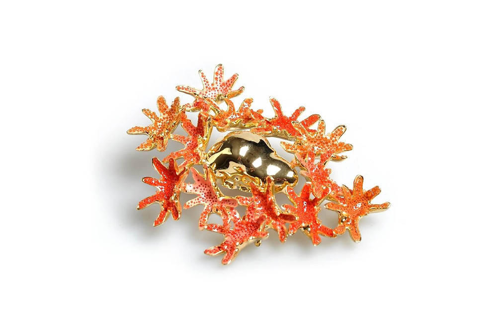 bright orange and red coral brooch made from gold and enamel