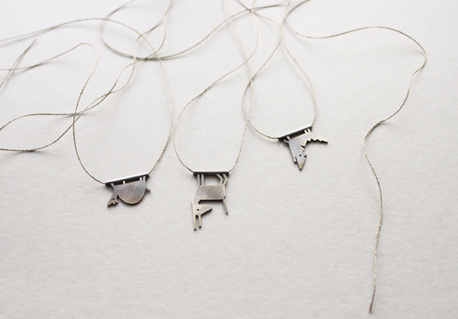 small animal necklaces hanging upside down on string
